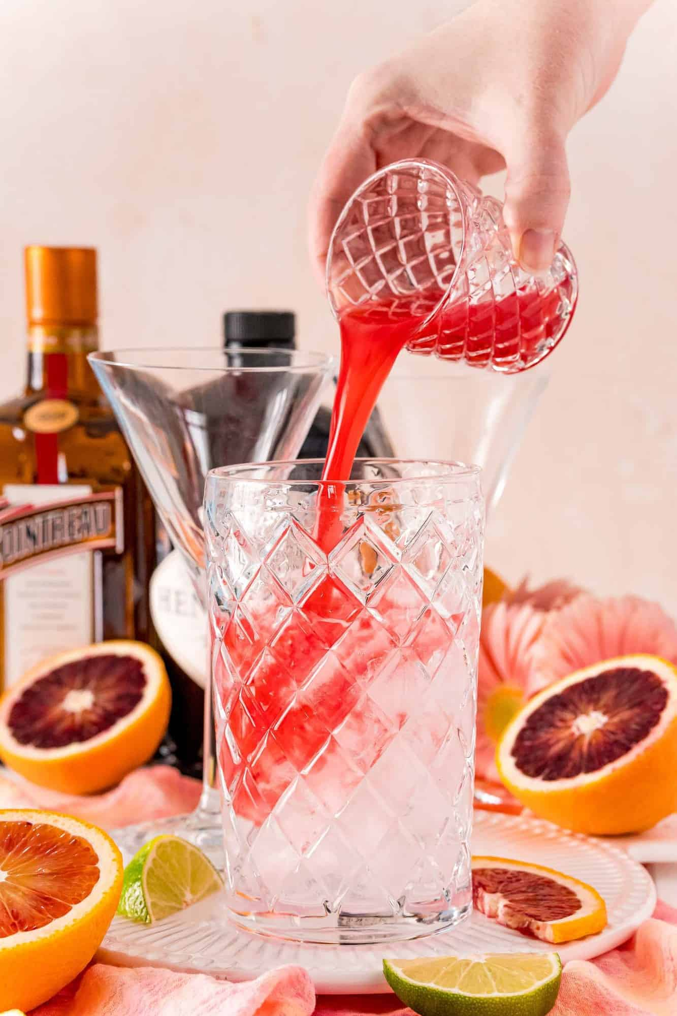 Blood orange juice being poured into a martini glass.
