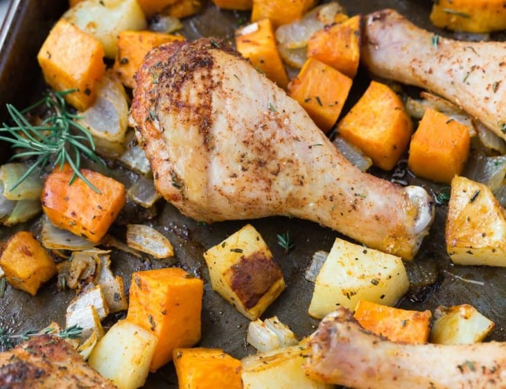 Chicken drumsticks and cubed potatoes and sweet potatoes on a sheet pan.
