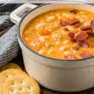 """Soup in a white two-handled bowl, text overlay reads """"homemade bean and bacon soup, rachelcooks.com"""""""