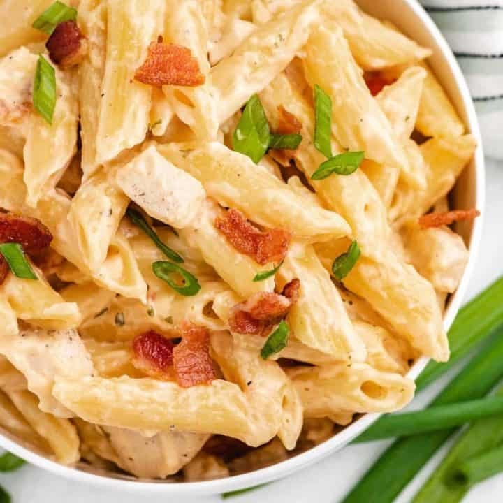 Pasta with chicken, cheese sauce, bacon, and green onions, in a white bowl.