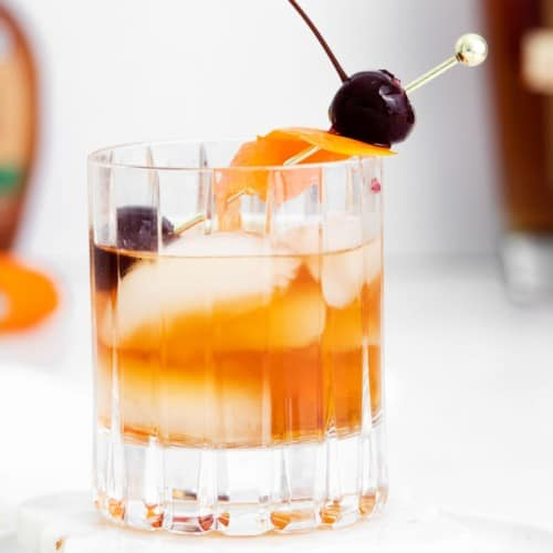 An old fashioned cocktail on ice with an orange peel and cherries.