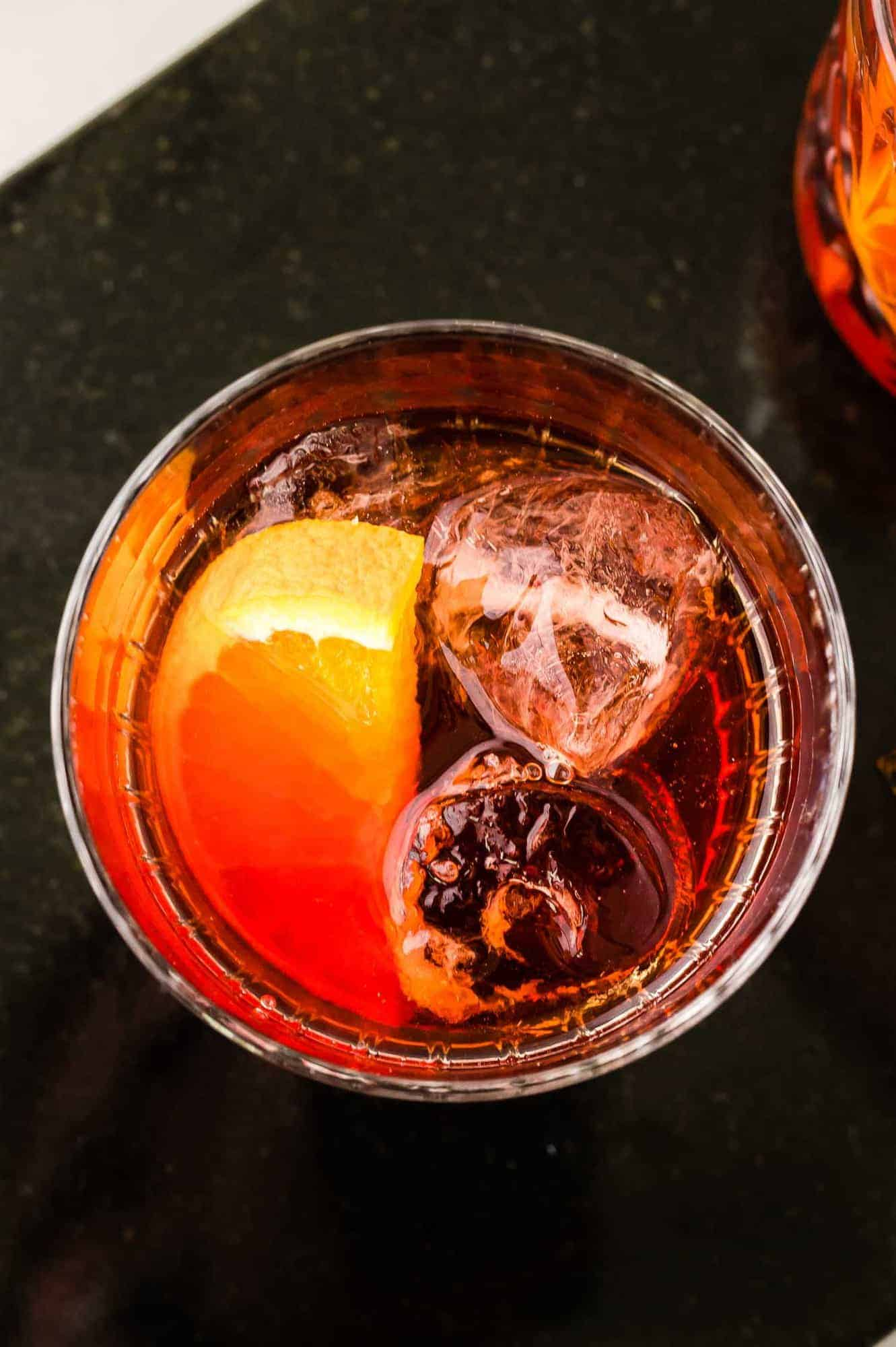 Overhead view of a drink with ice and an orange slice, on a black background.