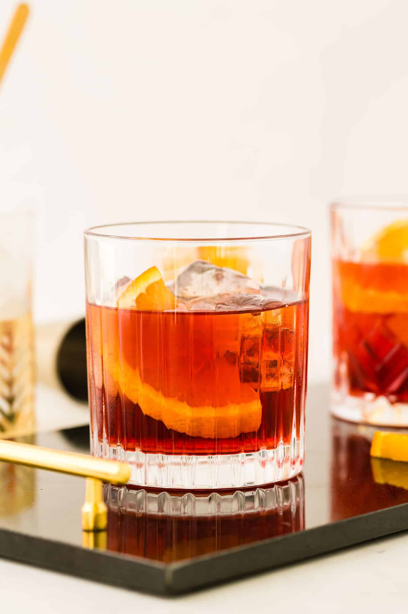 Dark red beverage in a short glass, with ice and an orange slice.