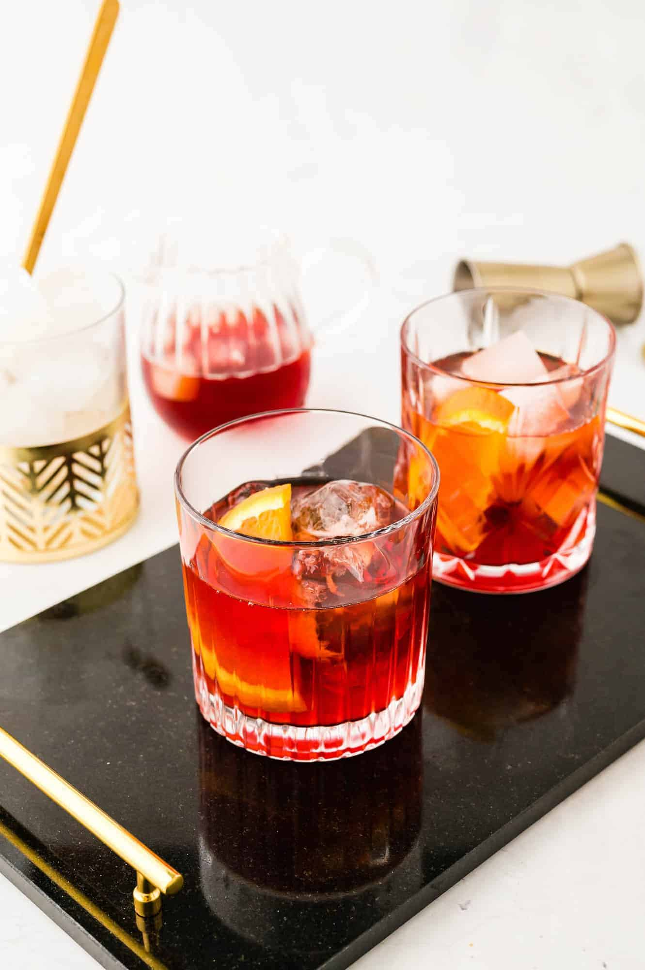 Two cocktails on a black tray.