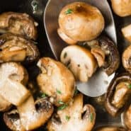"""Cooked mushrooms in a pan, text overlay reads """"sauteed mushrooms with white wine, rachelcooks.com"""""""