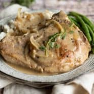 Pork on a plate with mushroom gravy, topped with fresh thyme.