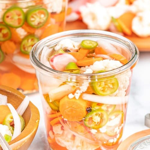 Mixed vegetables in a glass jar with liquid.