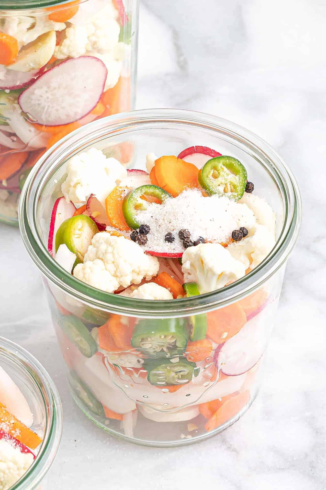 Cut vegetables, topped with sugar, salt, and peppercorns, in a glass jar.