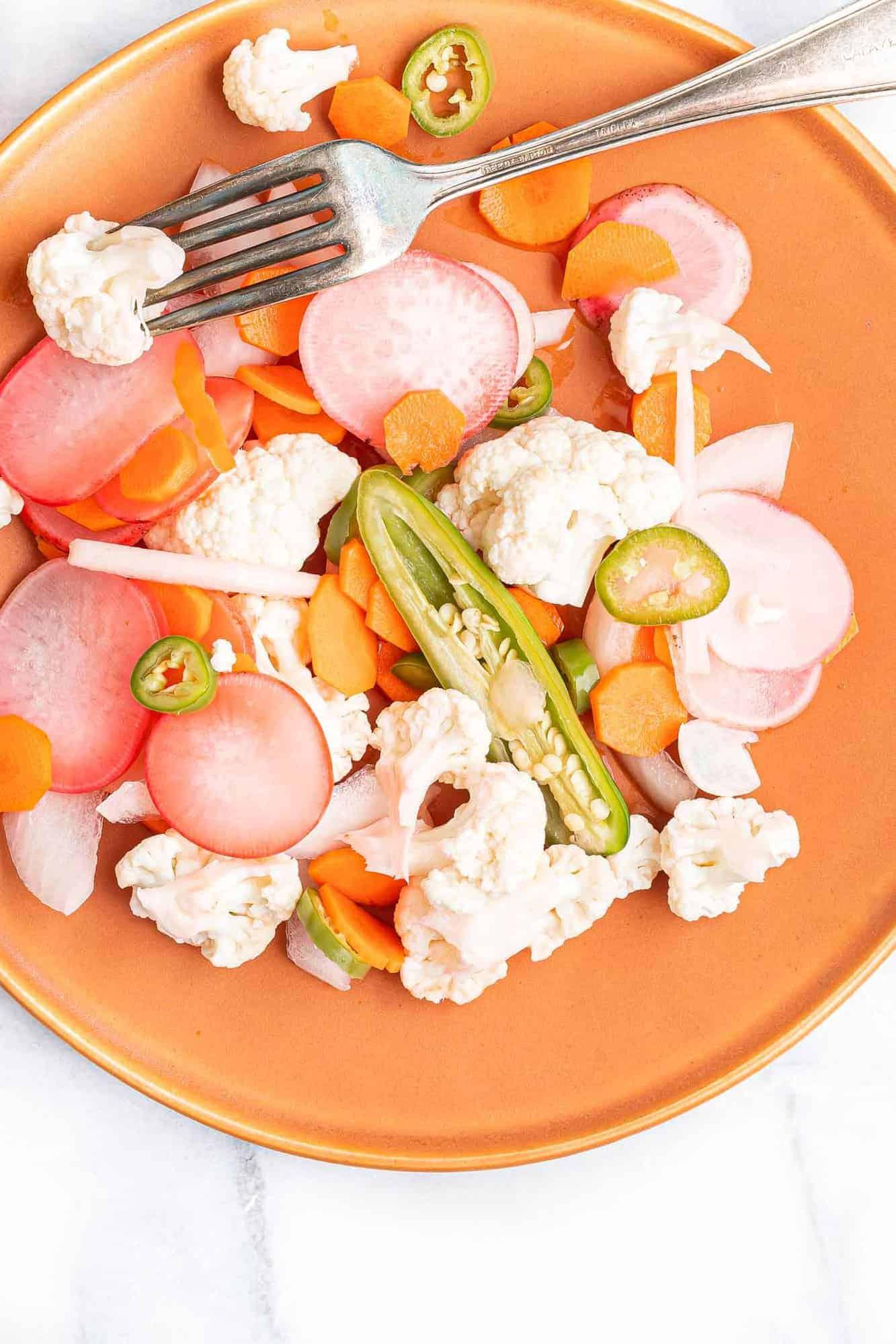 Pickled vegetables on a reddish orange plate.