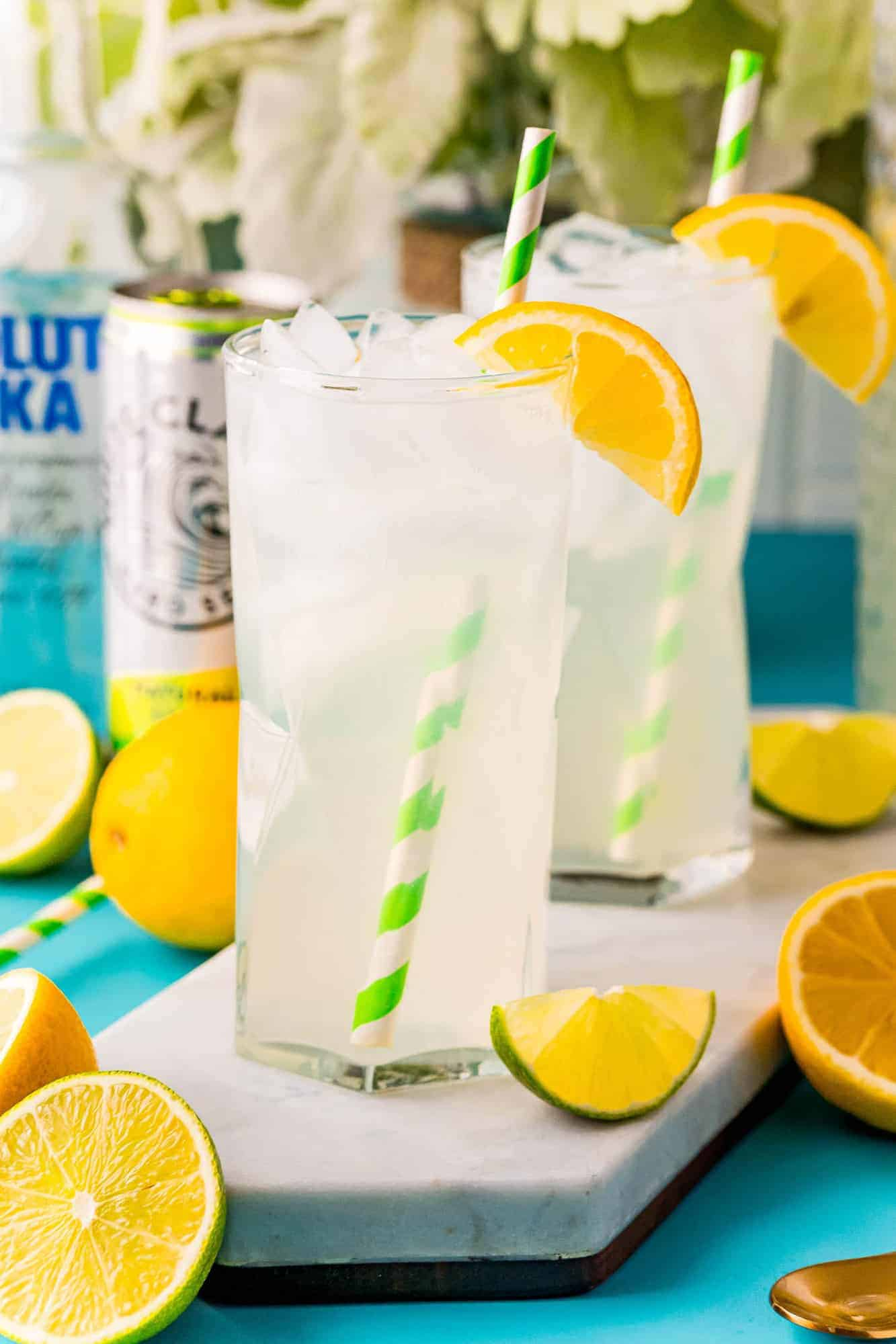 Two tall glasses of lemonade with green and white straws, a can of white claw in the background.