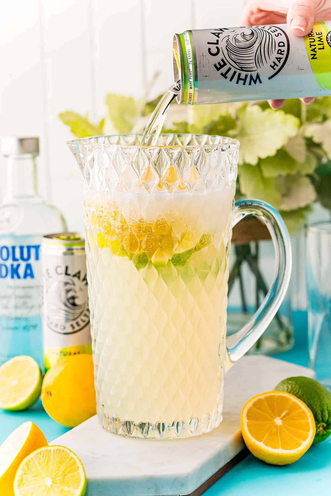 White claw being poured into a large pitcher of lemonade.