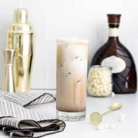 A white russian in a tall glass with supplies to make it in the background.