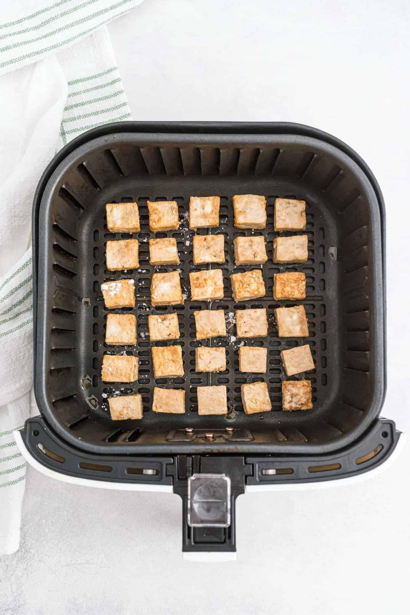 Tofu in an air fryer basket.