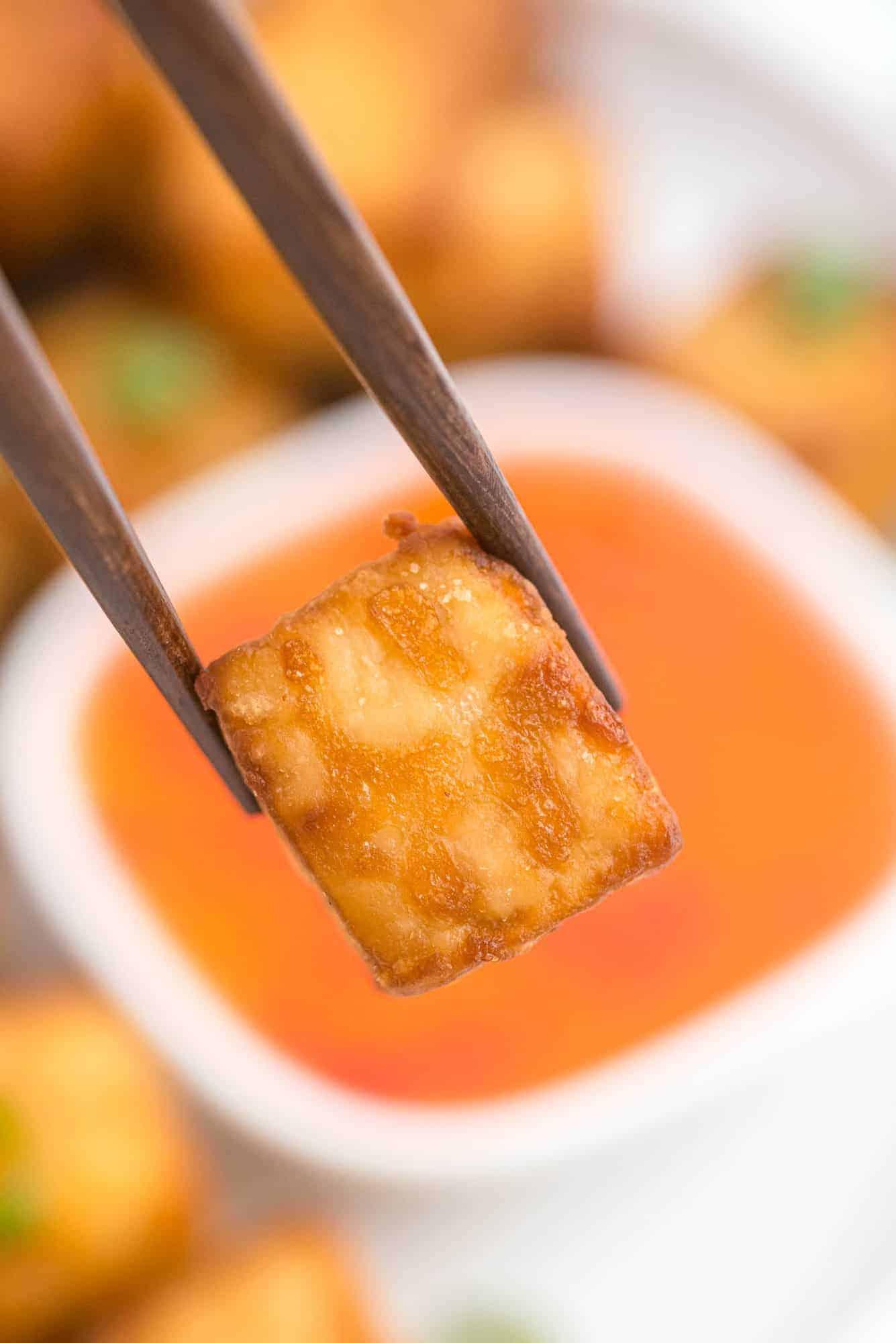Crispy piece of tofu held between brown chopsticks.
