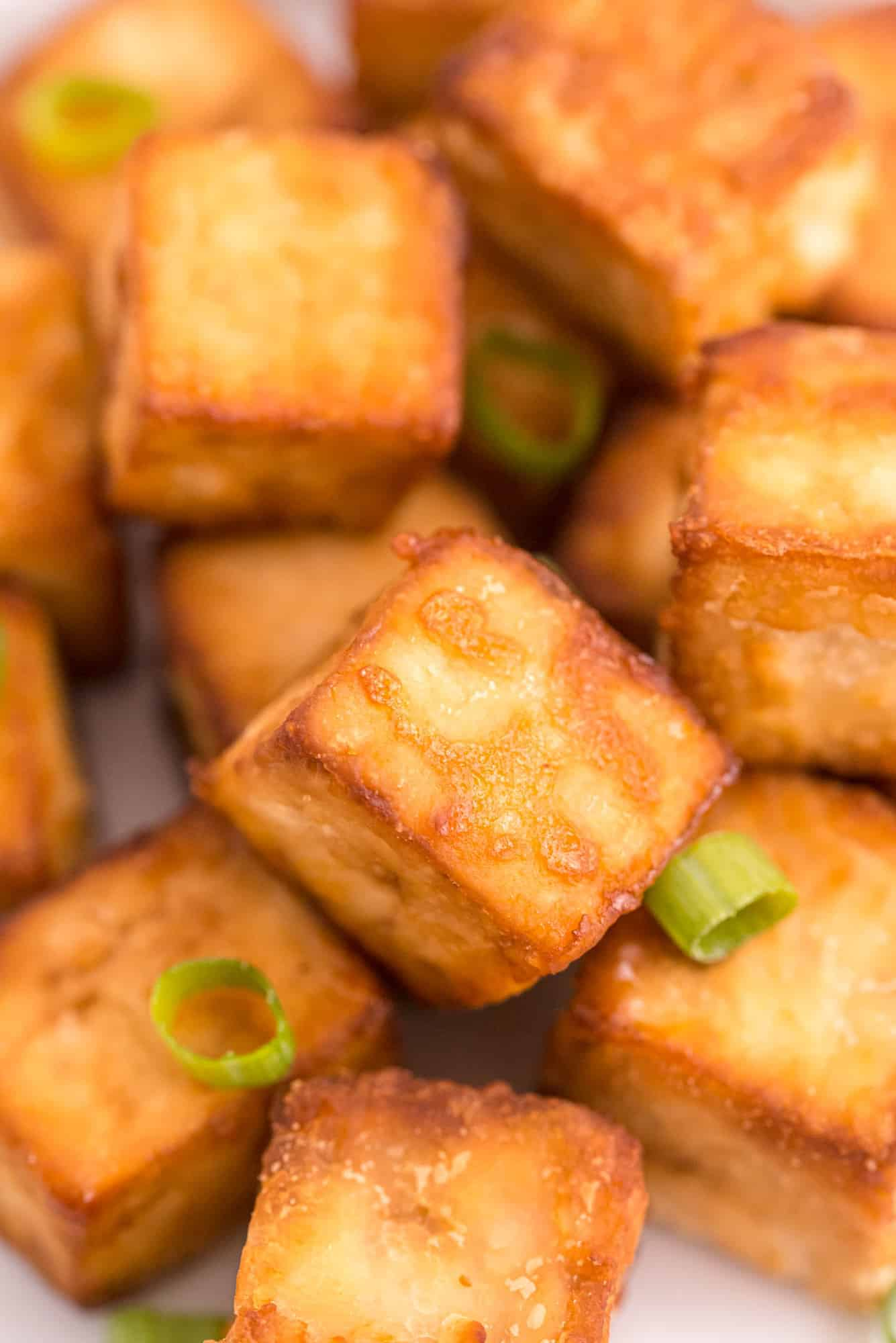 Close up of cubed, crispy tofu on a plate, topped with green onions.