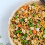 Overhead view of fried rice topped with sliced green onions.