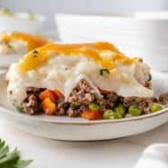 Slice of shepherd's pie on a white plate with a baking dish in the background.