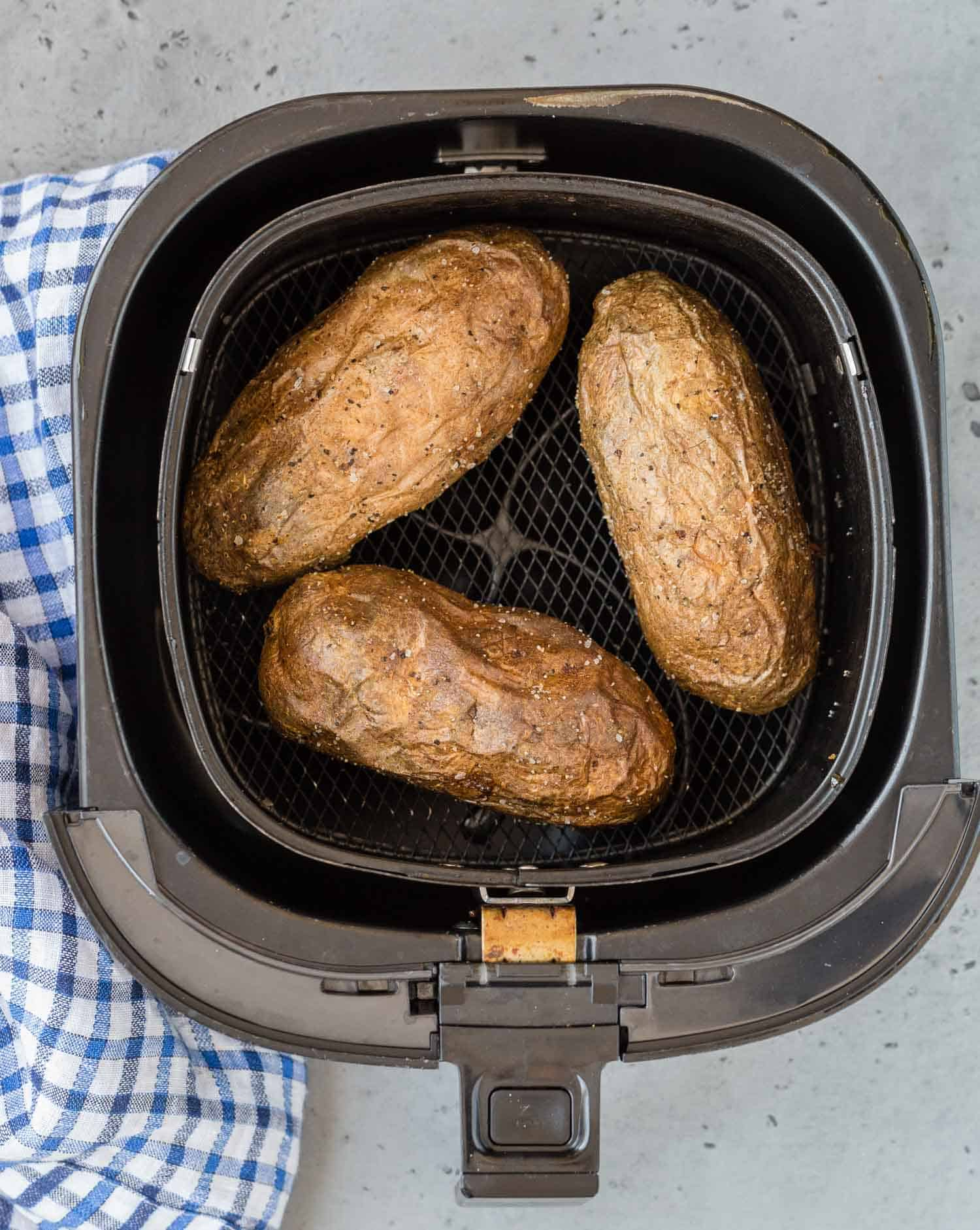 Overhead view of baked potatoes in an air fryer.