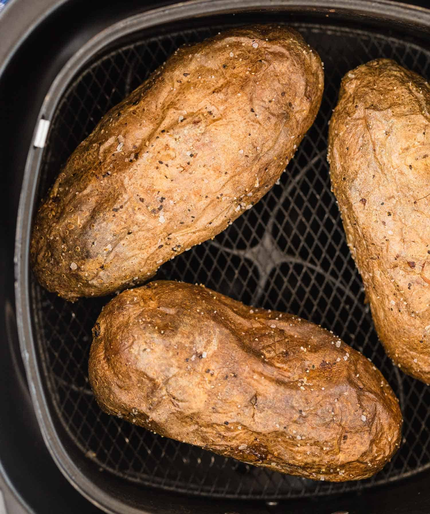 Close up of baked potatoes in an air fryer basket.
