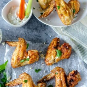 Golden brown chicken wings topped with fresh parsley.