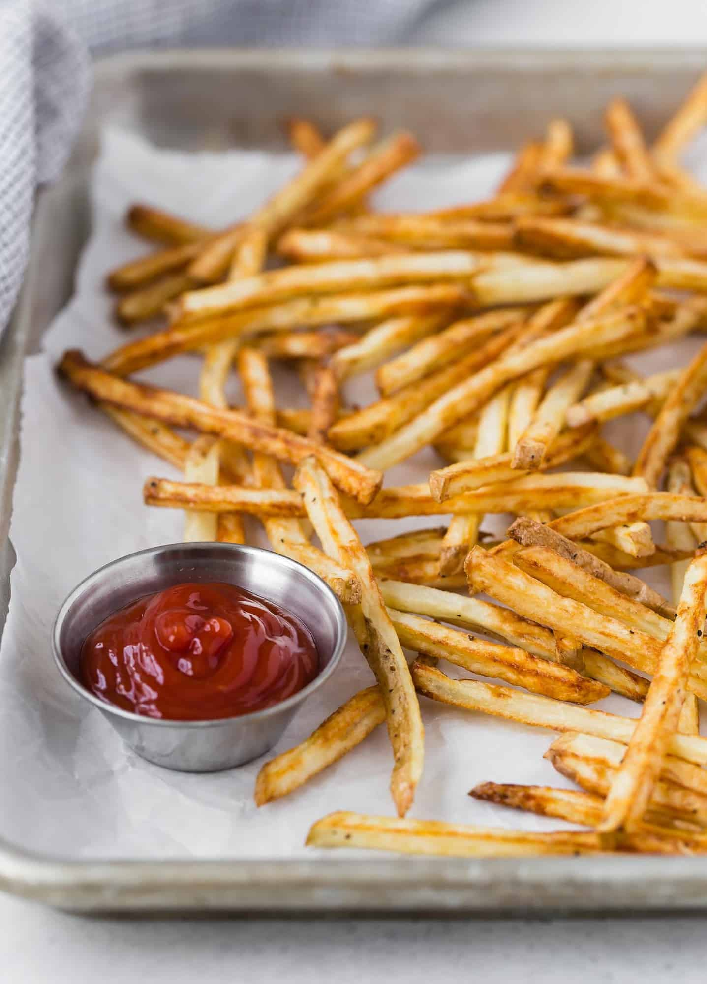 Crispy french fries made in an air fryer, on a metal tray with a cup of ketchup also pictured.