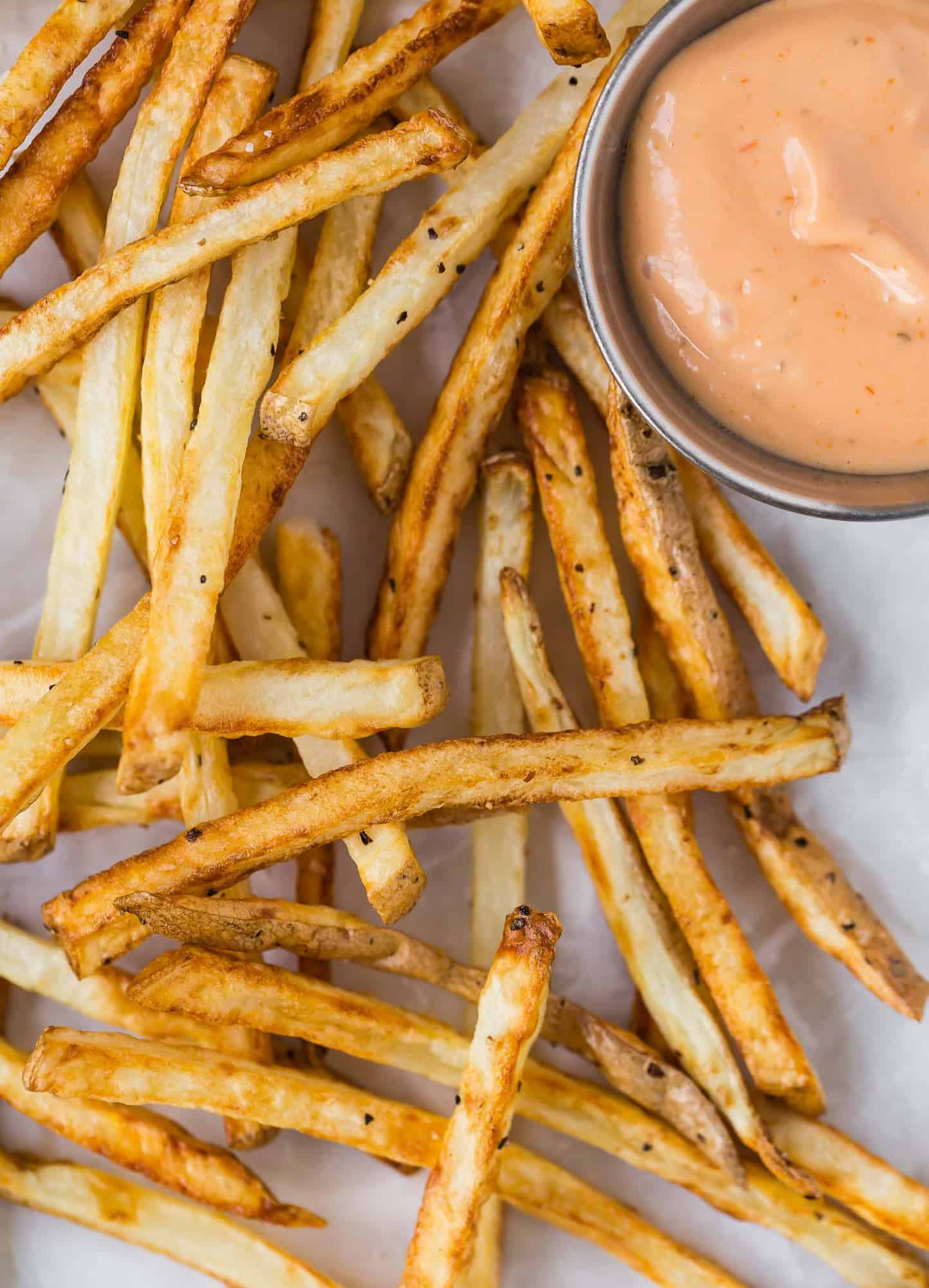 Overhead view of crispy fries with dipping sauce.
