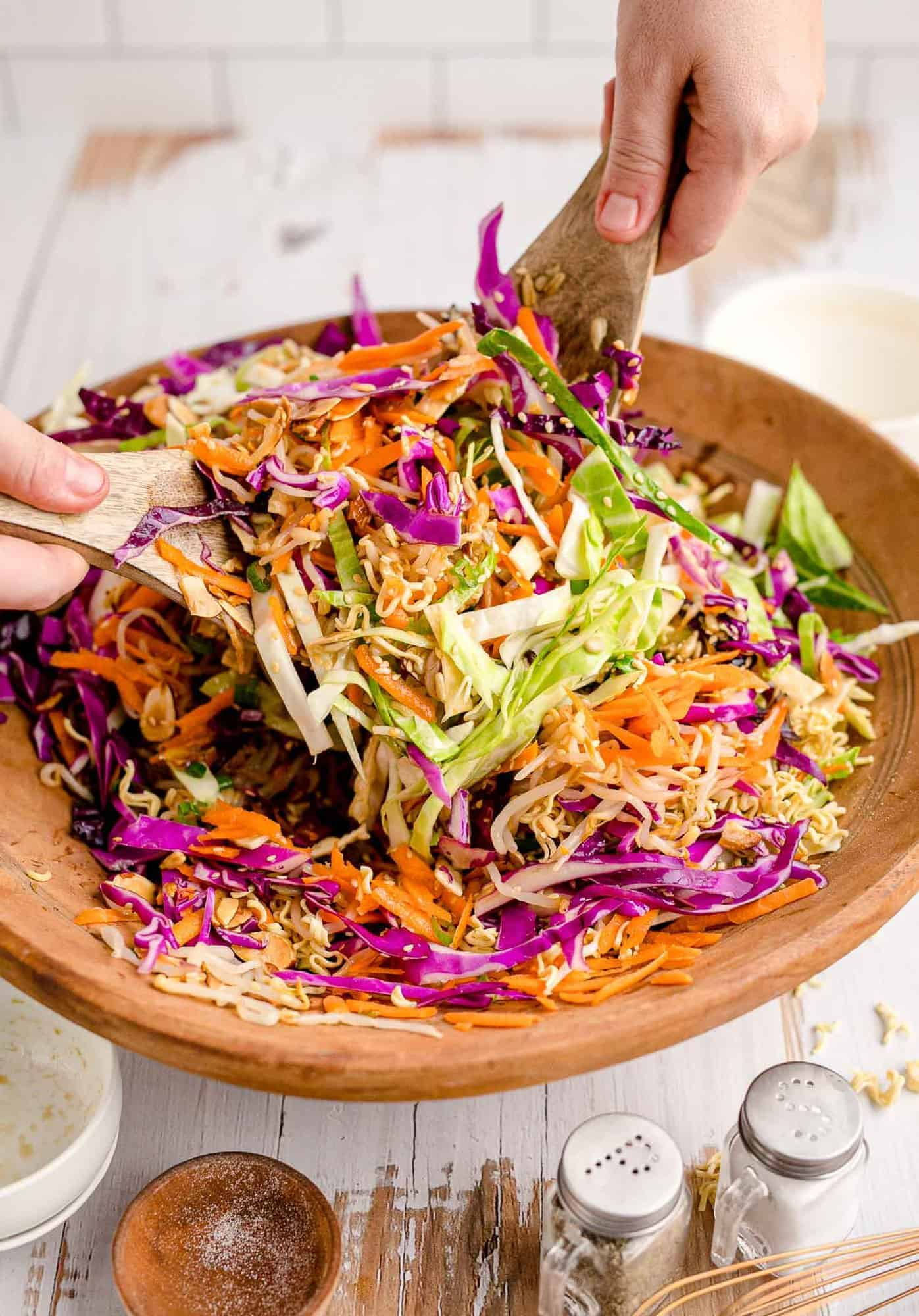 Large salad in a wooden bowl being tossed with handheld salad tongs.