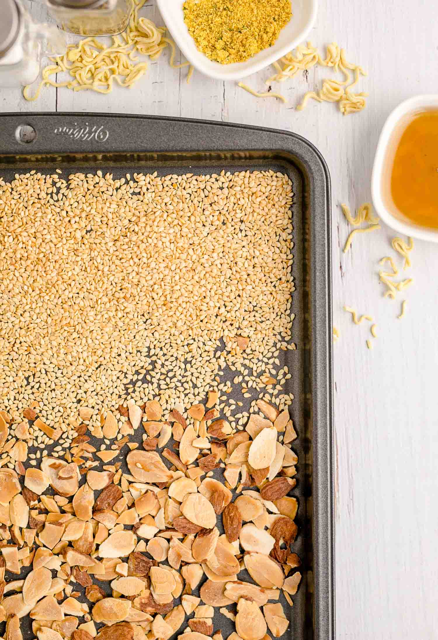 Toasted almonds and sesame seeds on a sheet pan.
