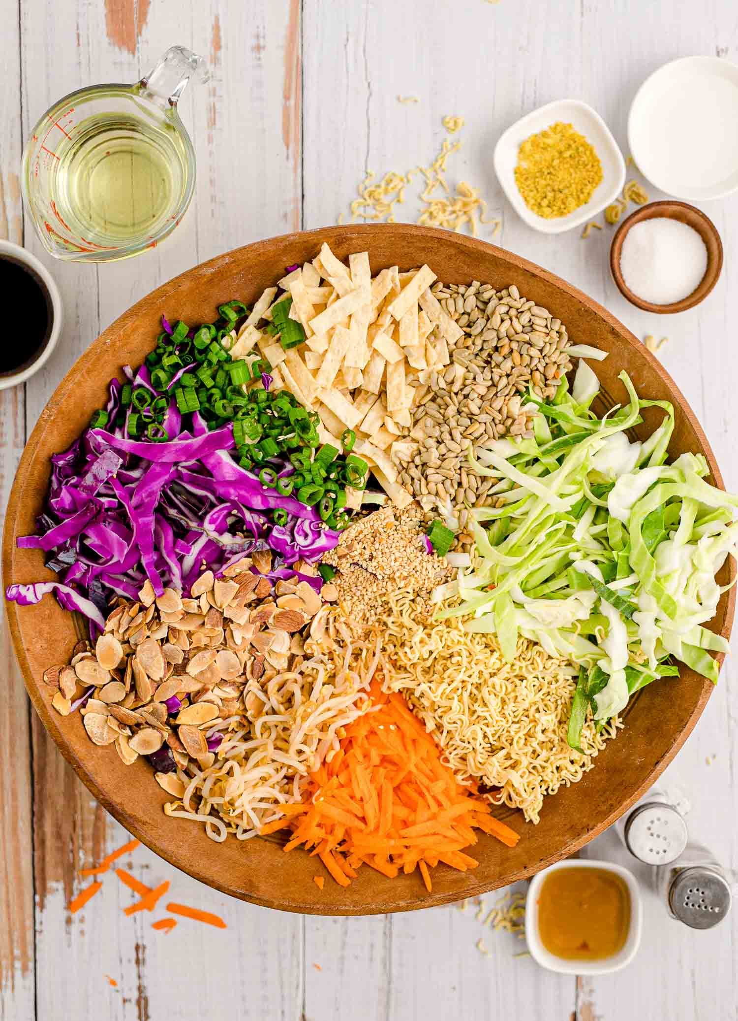 Unmixed ingredients in a large wooden bowl.
