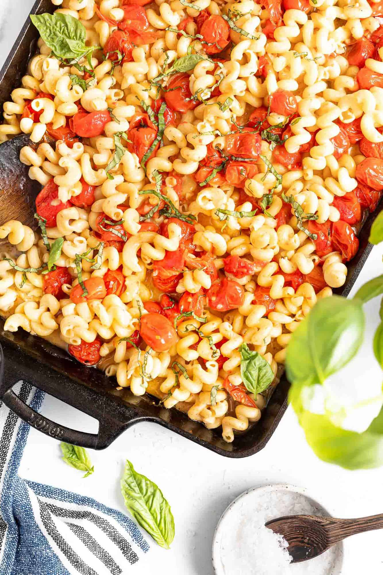 Black baking dish filled with pasta, tomatoes, and basil.