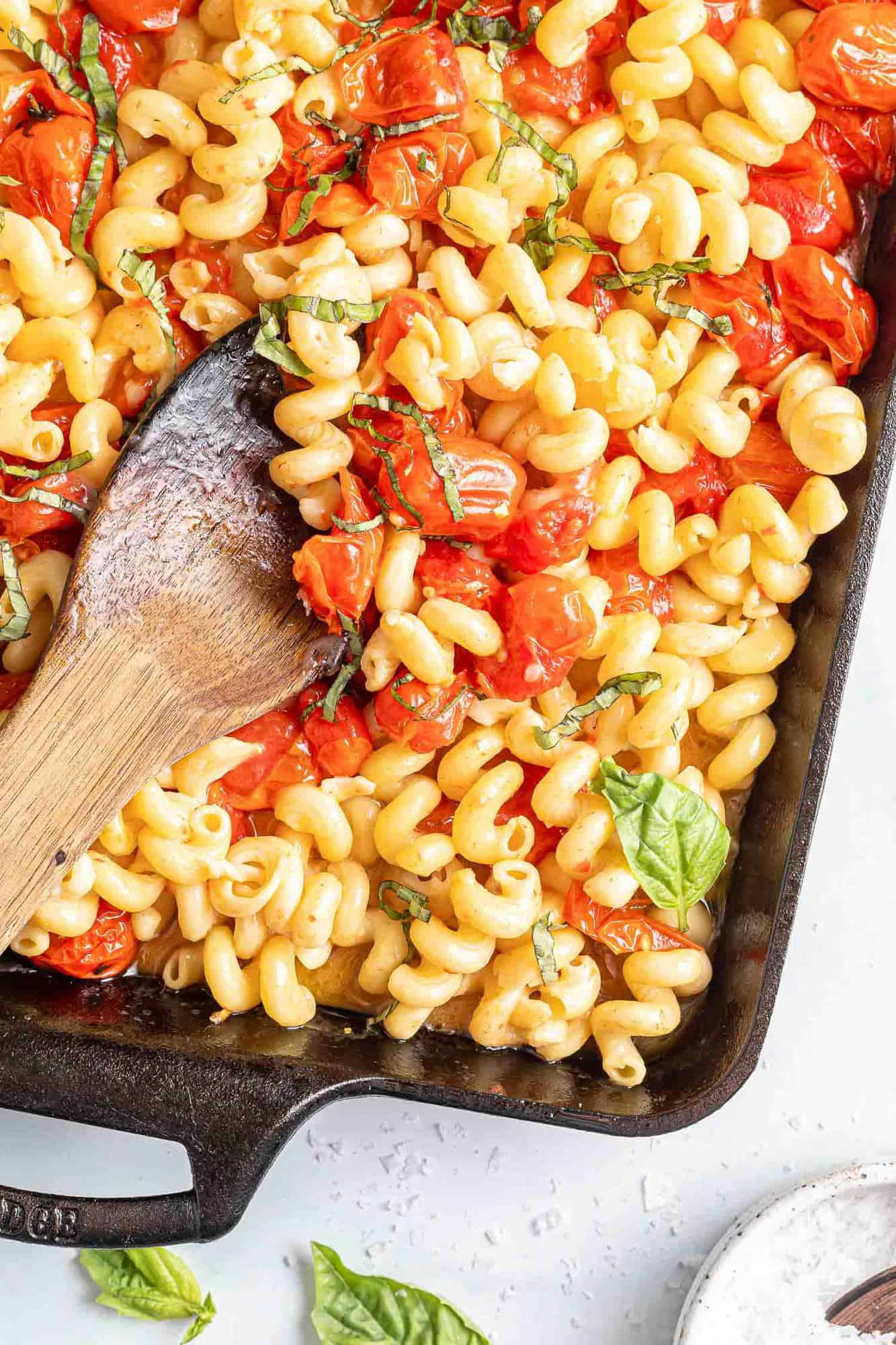 Pasta with tomatoes, basil, and feta cheese in a black baking dish.