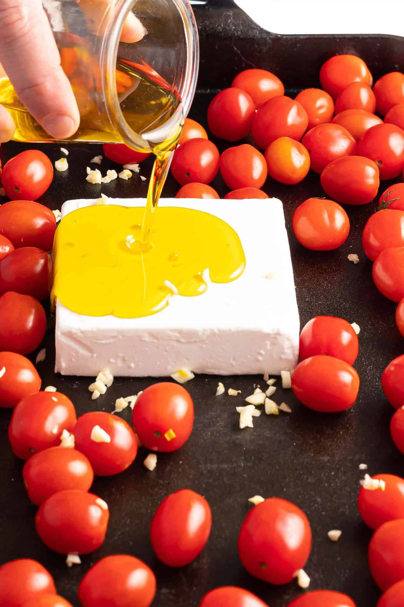Olive oil being poured on a block of feta.