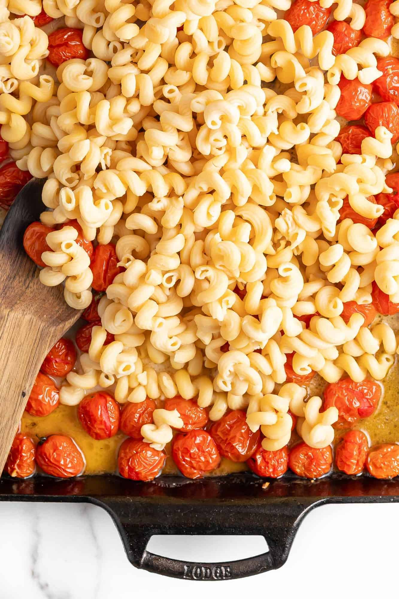 Pasta being stirred into roasted tomatoes and feta in a baking dish.