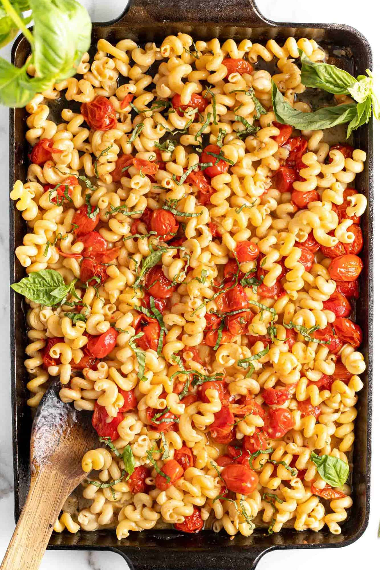 Pasta and tomatoes in a feta sauce, sprinkled with fresh basil.