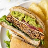 Black bean burger on a plate with chips, cut in half.