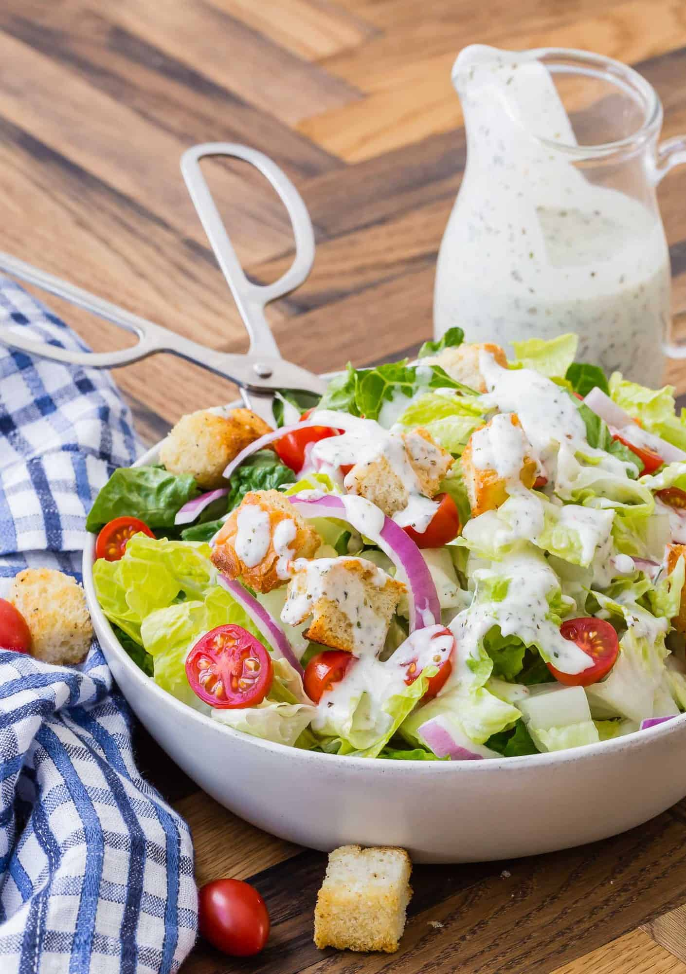 Tossed salad with tongs, small glass pitcher of creamy dressing in the background.