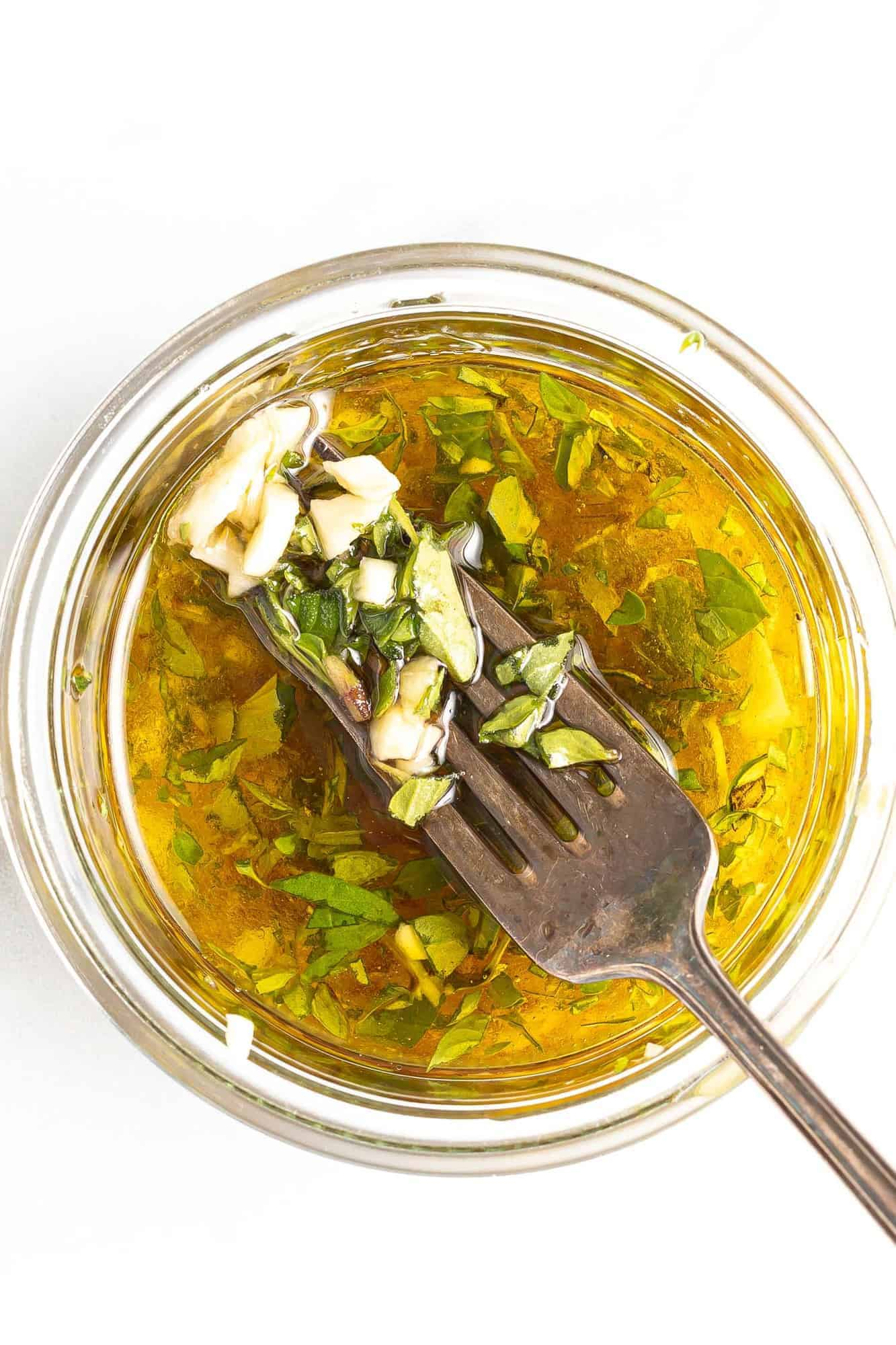 Dressing in a jar with a fork showing some ingredients.