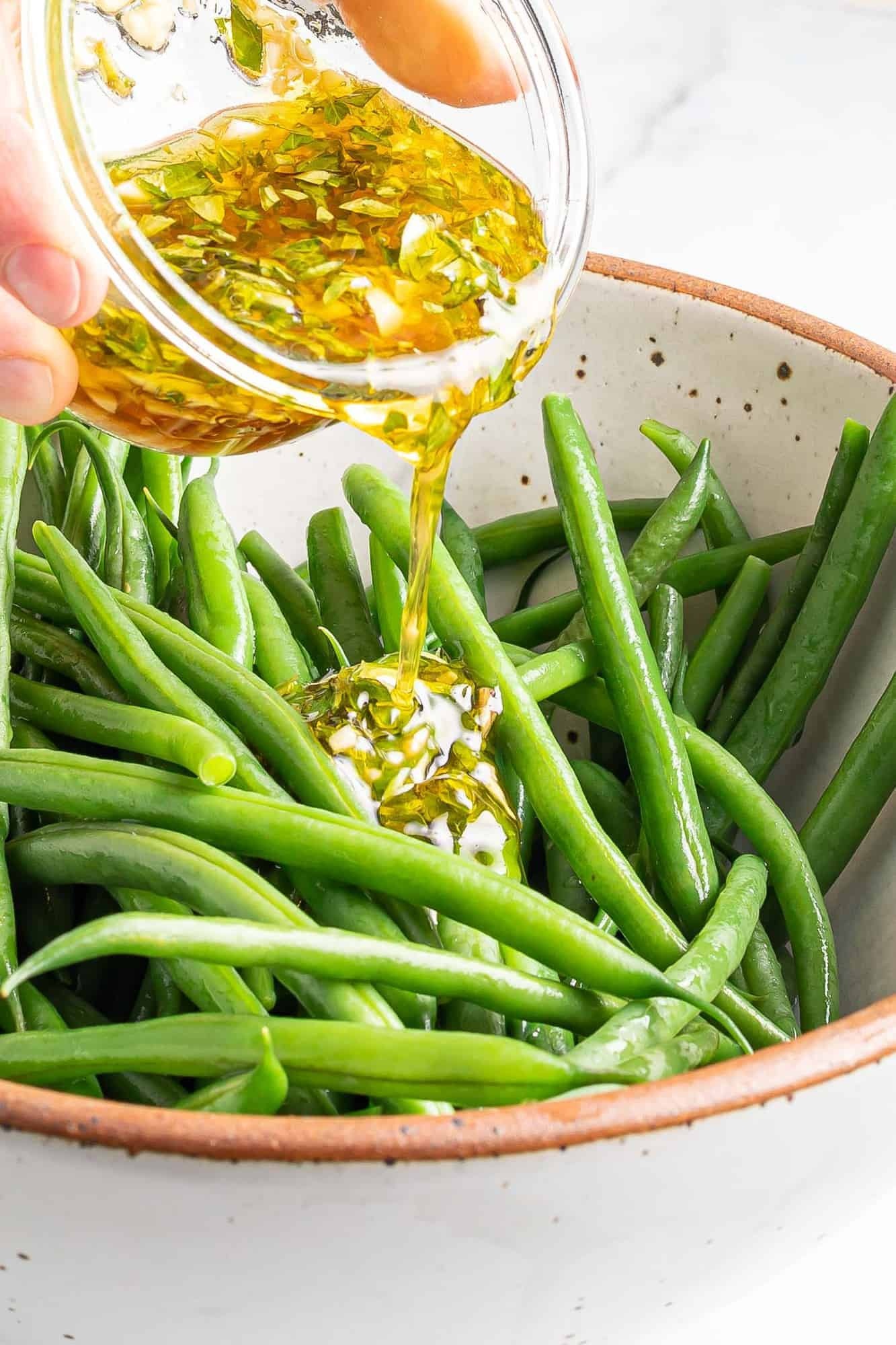 Dressing being poured on green beans.