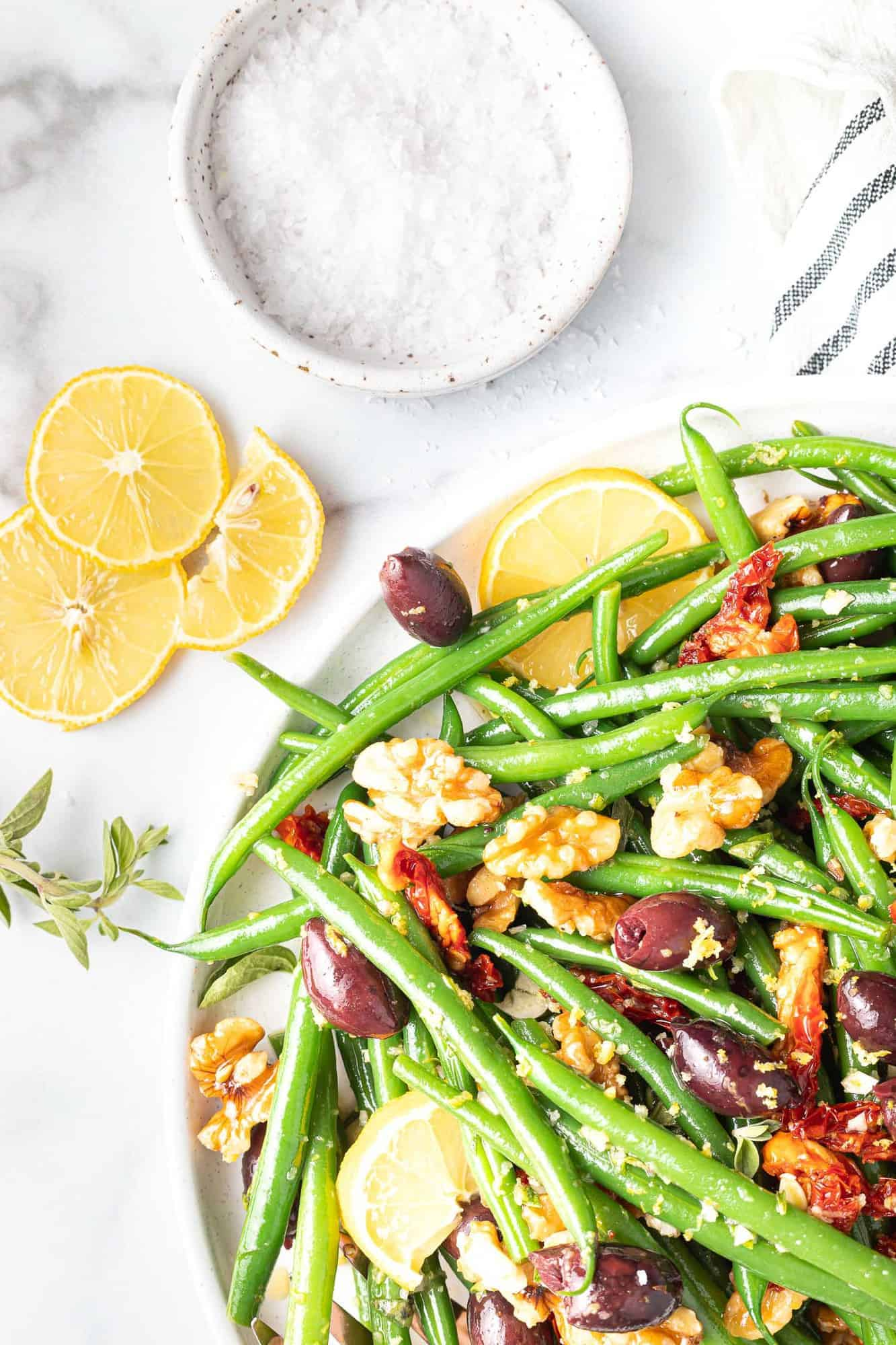 Colorful green bean salad, lemon slices and salt nearby.