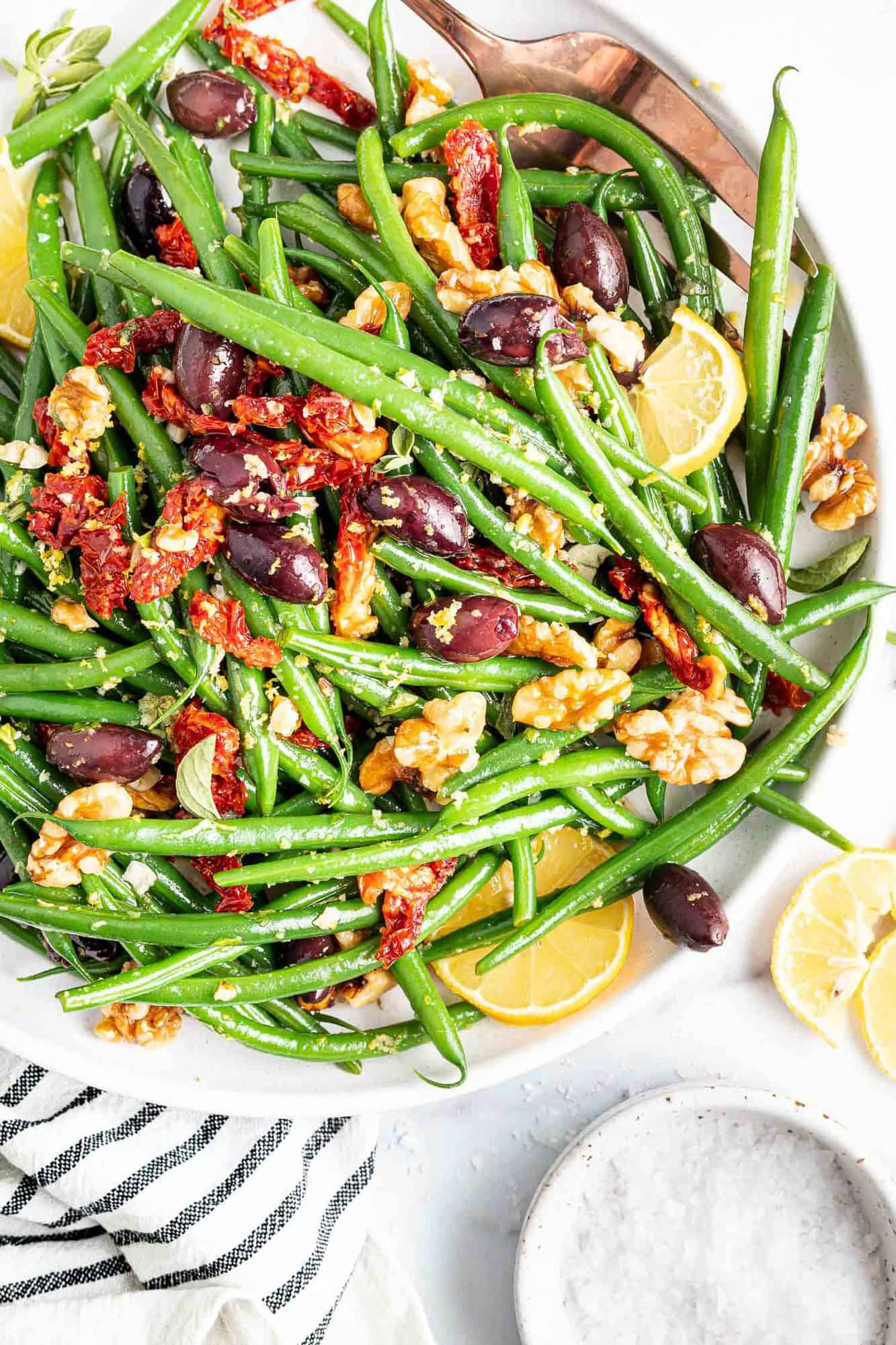 Green beans in a large white bowl with sun dried tomatoes, kalamata olives, and walnuts.