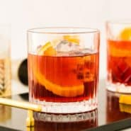 Dark red cocktail with ice and an orange slice.