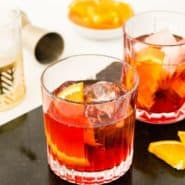 "Dark red cocktail with an orange in it, text overlay reads ""how to make the perfect negroni, rachelcooks.com"""
