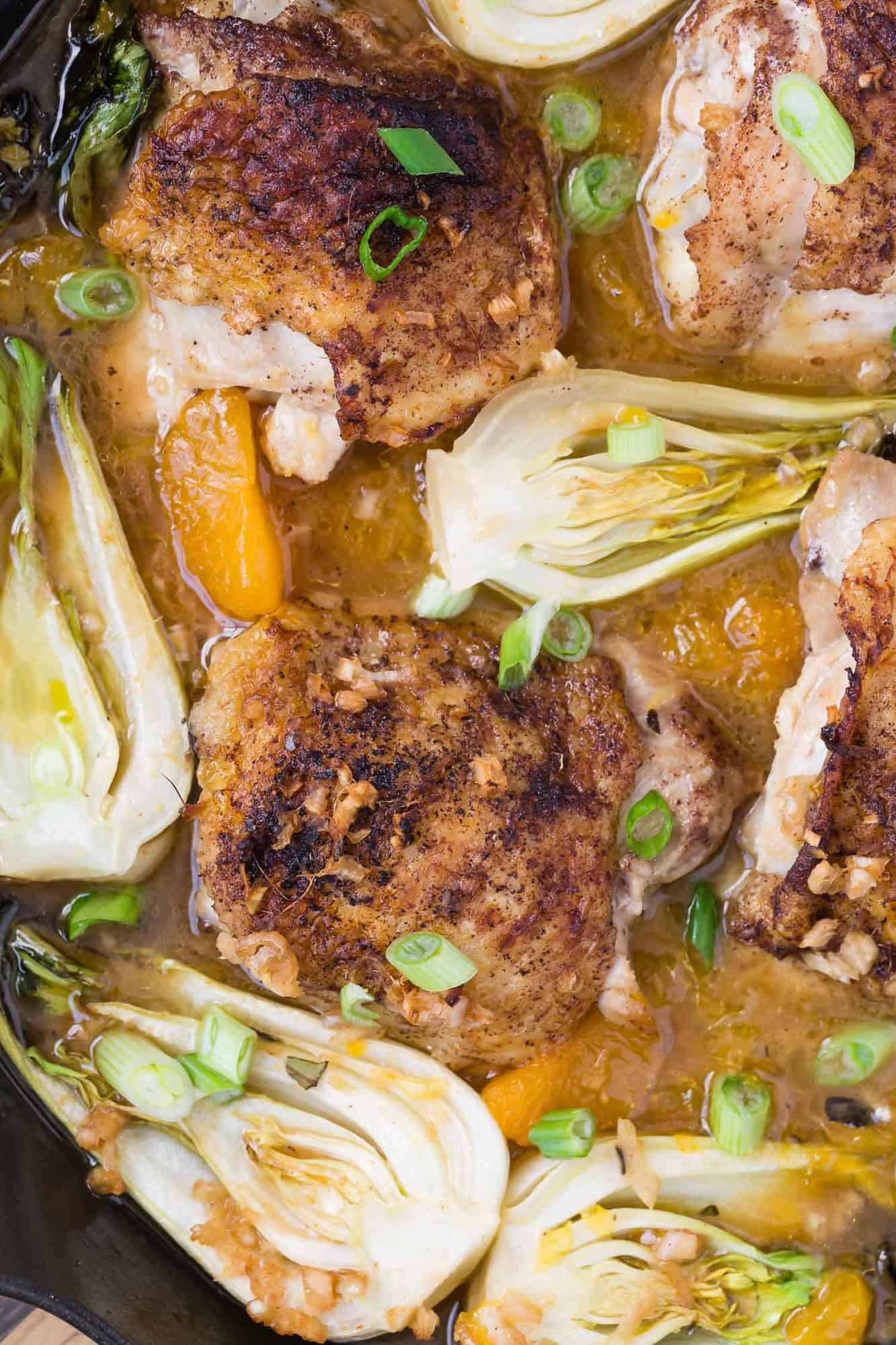 Close up of chicken and bok choy in a pan.
