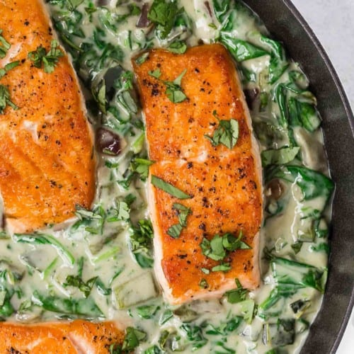 Overhead view of seared salmon settled in a bed of a spinach cream sauce.