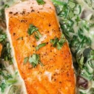 """Overhead view of seared salmon, text overlay reads """"salmon with spinach poblano cream sauce."""""""
