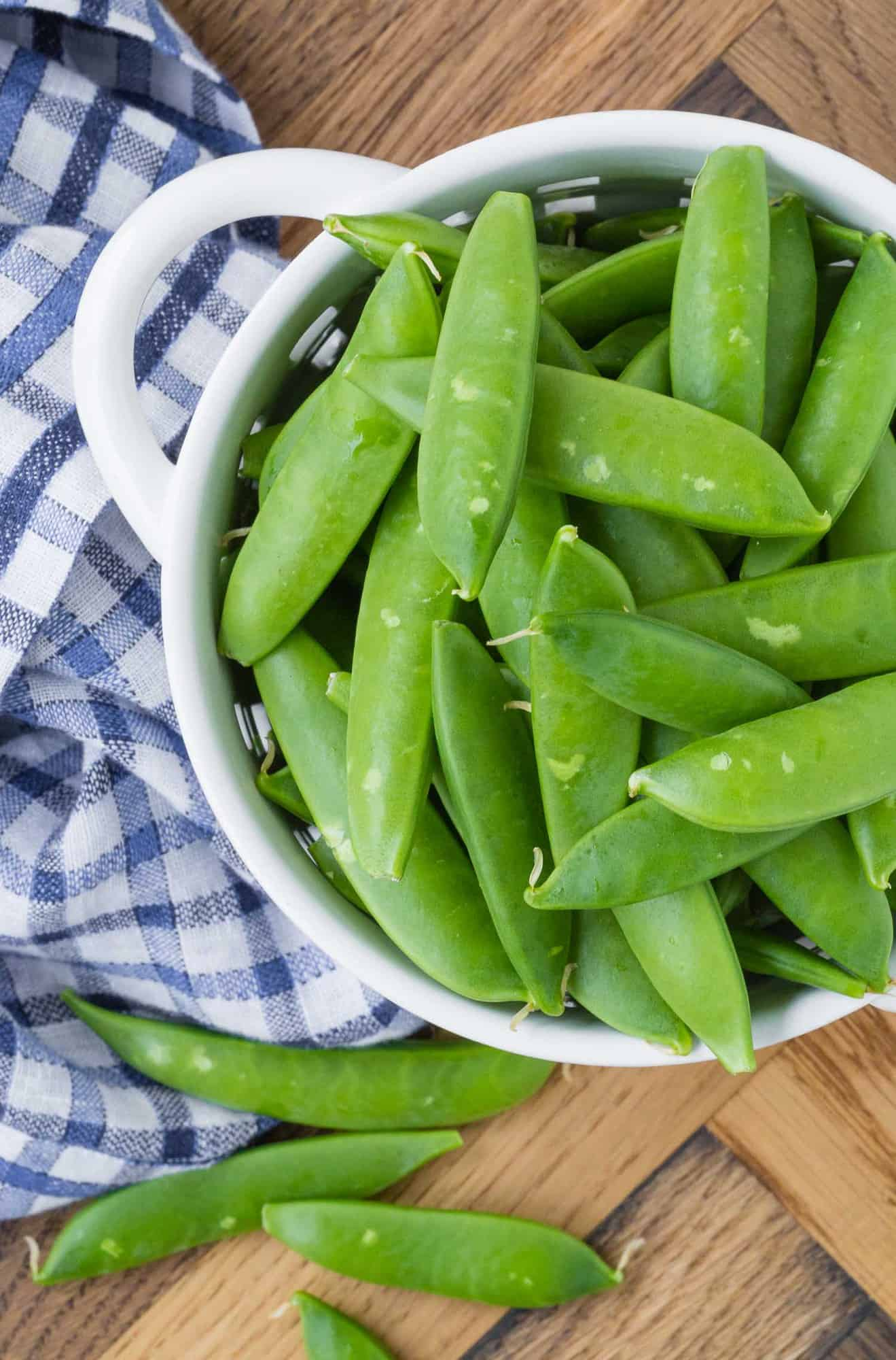 Overhead view of a small white strainer full of raw sugar snap peas.