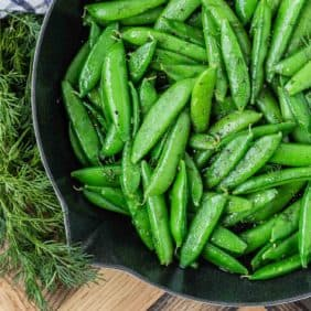 Bright green sugar snap peas in a black skillet, garnished with fresh dill.