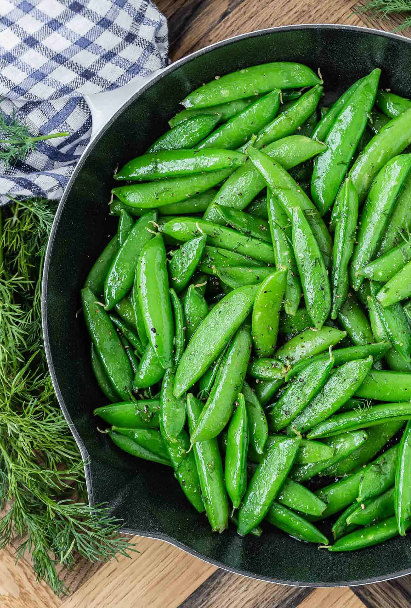 Cast iron pan with cooked sugar snap peas and fresh dill.