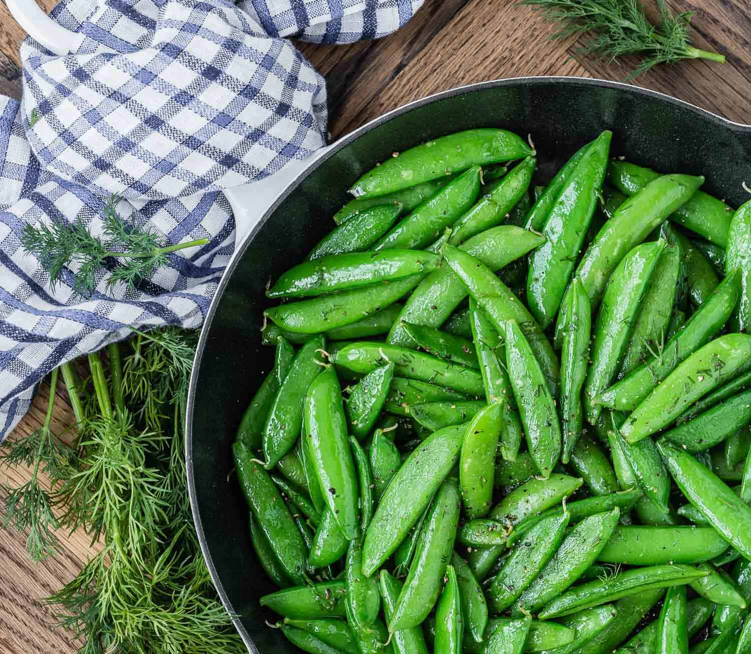 Cooked snap peas with dill in a pan on a wooden surface with a blue and white linen.