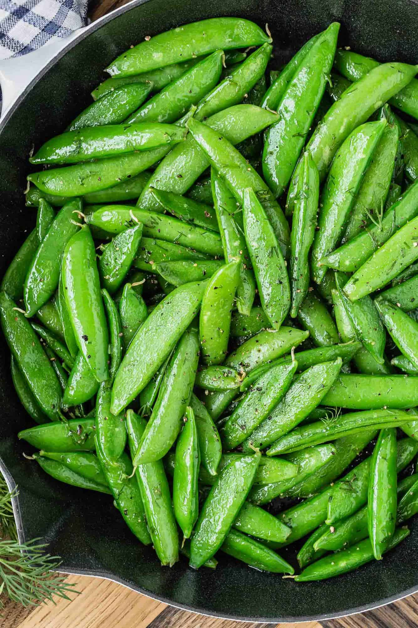 Close up of cooked snap peas in a black skillet.